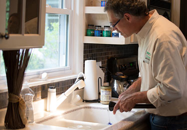 A home inspector checking the kitchen plumbing.